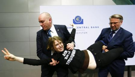Security officers carry away a protester who jumped on the table in front of the European Central Bank President Mario Draghi during a news conference in Frankfurt